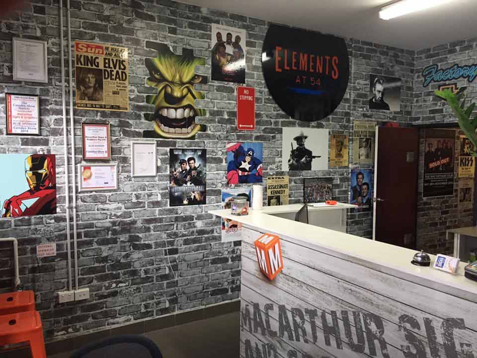 gray brick wall with posters on it and macarthur signs front desk