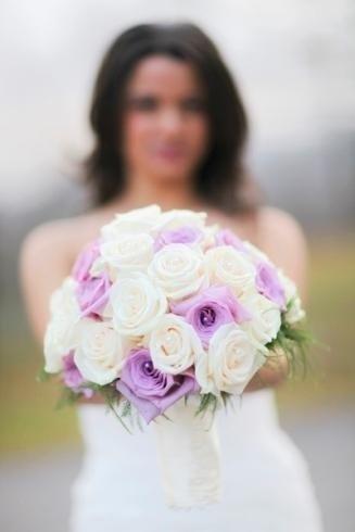 Il fioraio realizza bouquet da sposa con rose ornate di perle.
