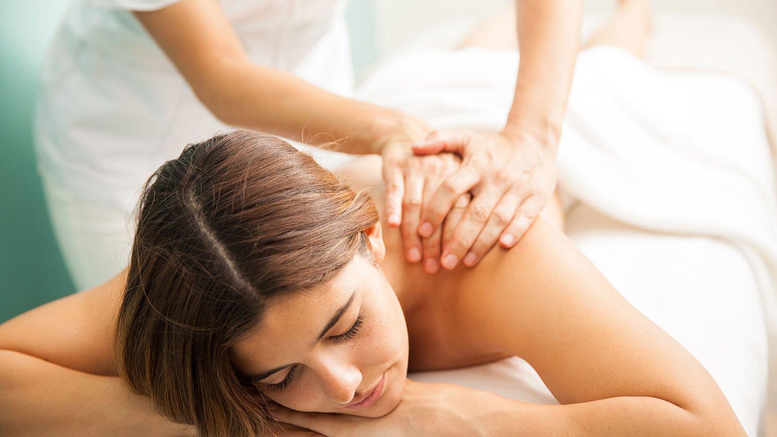 Due mani di una donna mentre fanno un massaggio alla spalla di una donna sdraiata su un lettino