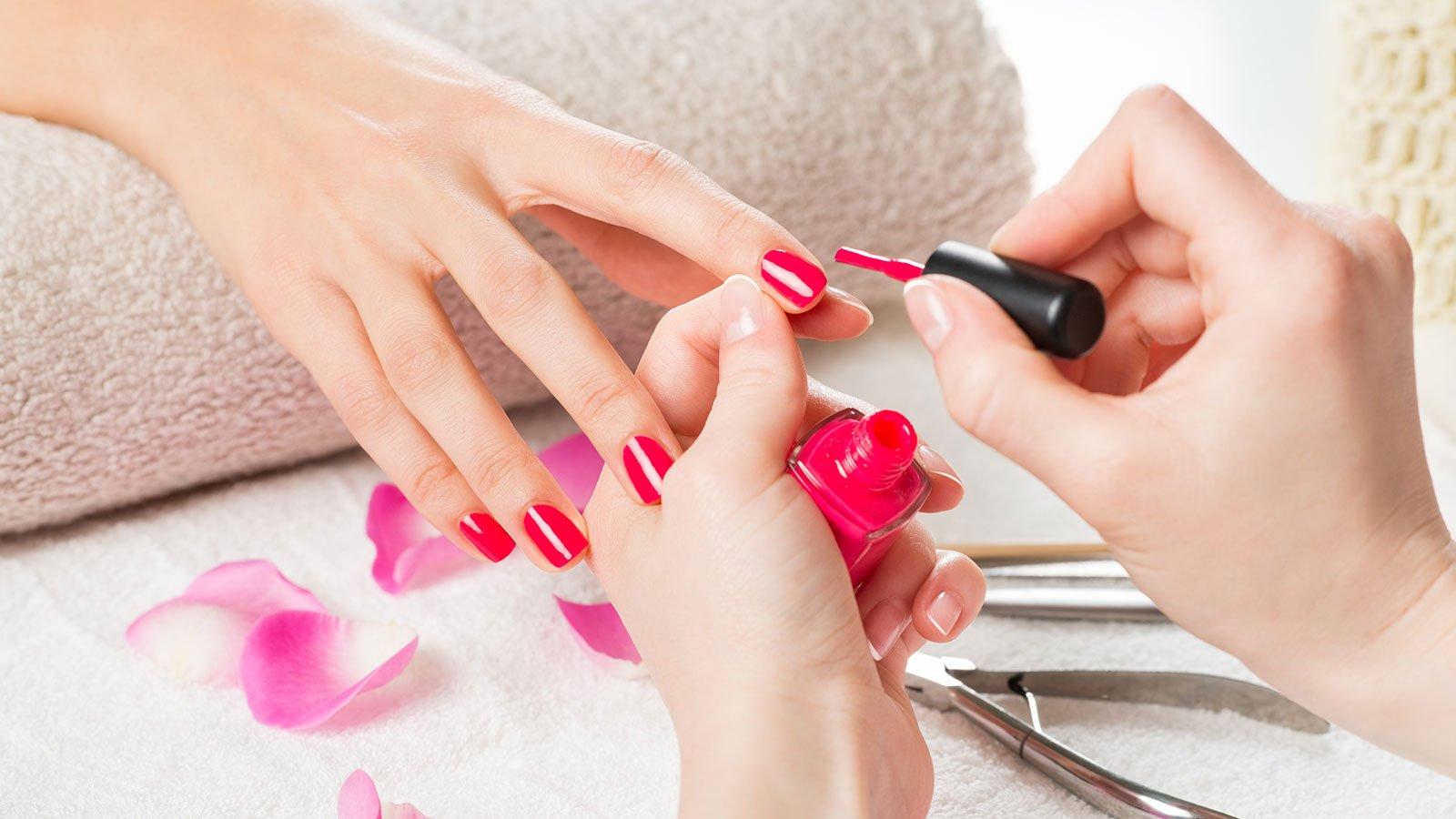 Due mani di una donna mentre applicano uno smalto di color rosso sulle unghie di un'altra donna