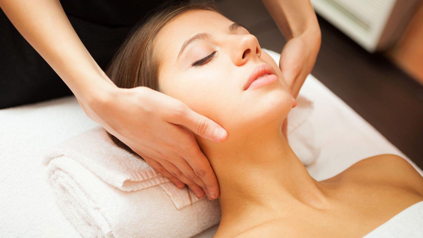 Due mani di una donna mentre fanno un massaggio al collo di una donna sdraiata su un lettino