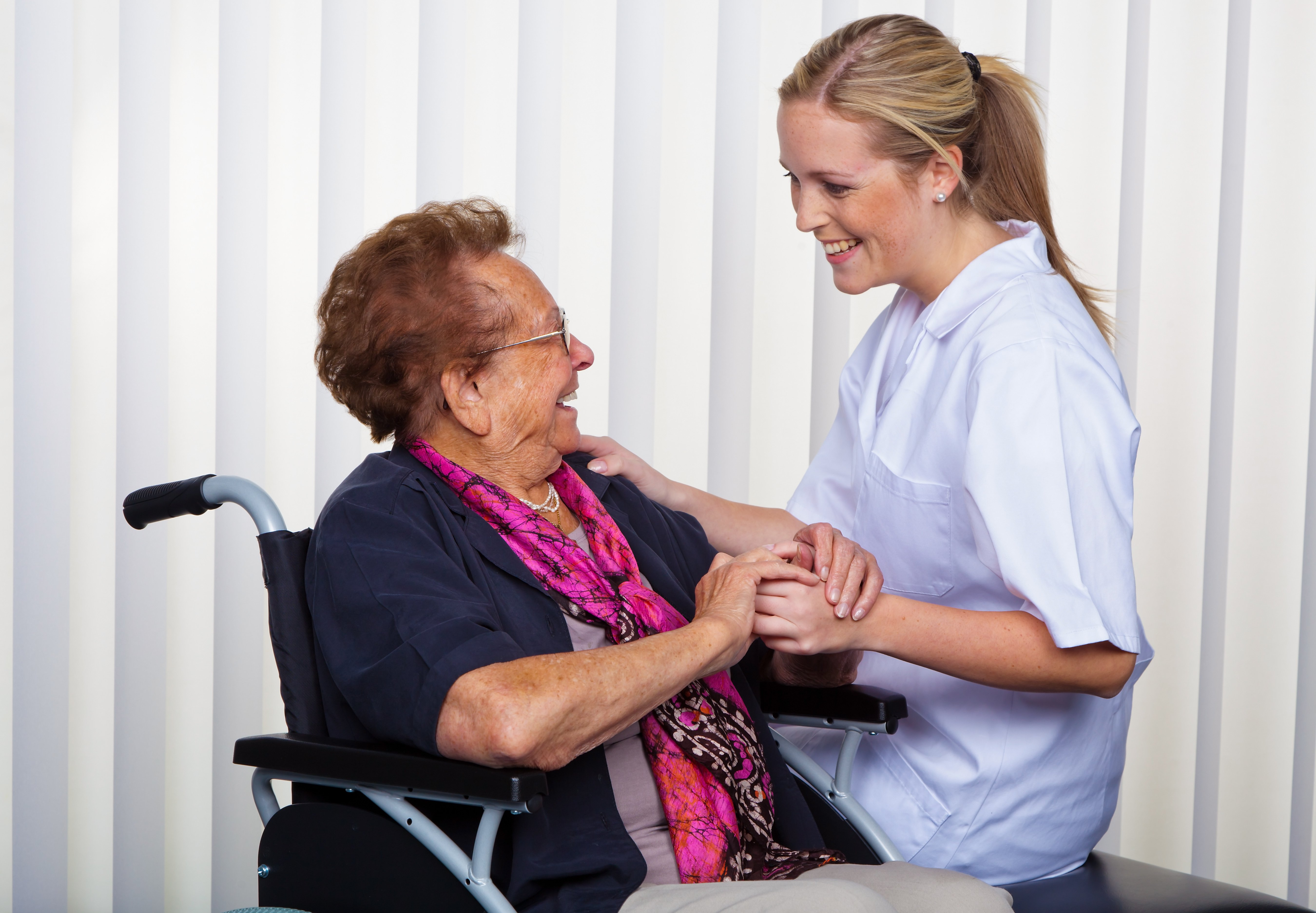 A lady sitting in a wheelchair, enjoying a laugh with a female carer