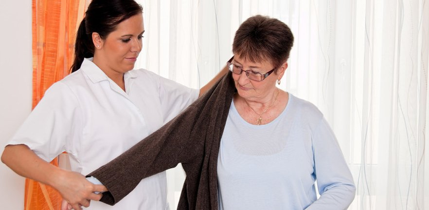 A carer helping a lady on with her robe