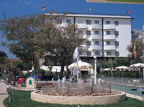 vista frontale di un albergo con giardino, alberi e fontana acqua