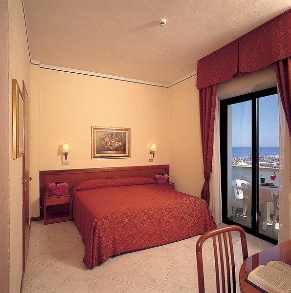 camera da letto con parete gialla e finestra in vetro