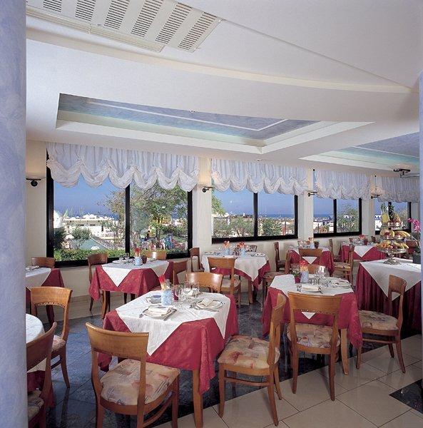 vista interna di ristorante con tavoli apparecchiati  e finestre in vetro
