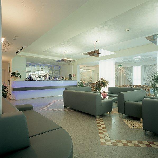 centralino dell albergo con divani, tavoli, pavimento in piastrelle e tende transparete