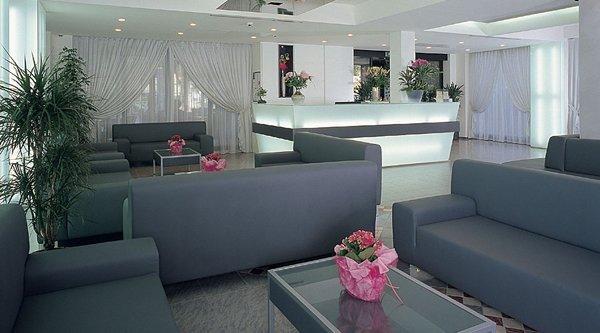 centralino del albergo con vasi di fiori, divani, tavoli e tende transparete