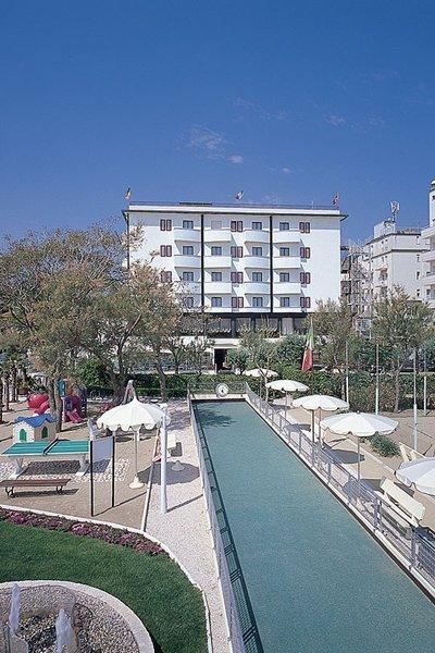 vista frontale di Hotel Delle Nazioni con giardino, ombrelloni e alberi
