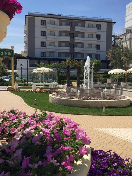 vista frontale di un albergo con giardino