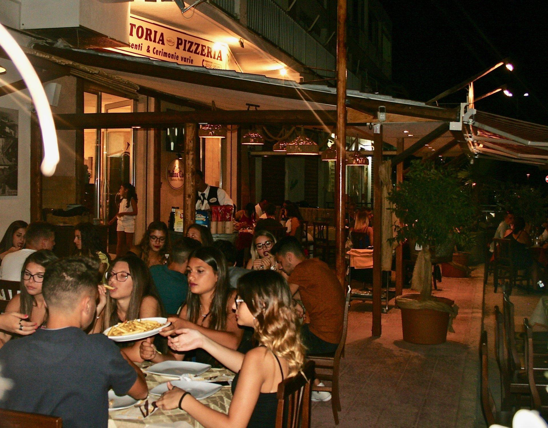 Esterno della pizzeria con dei cliente che mangiano