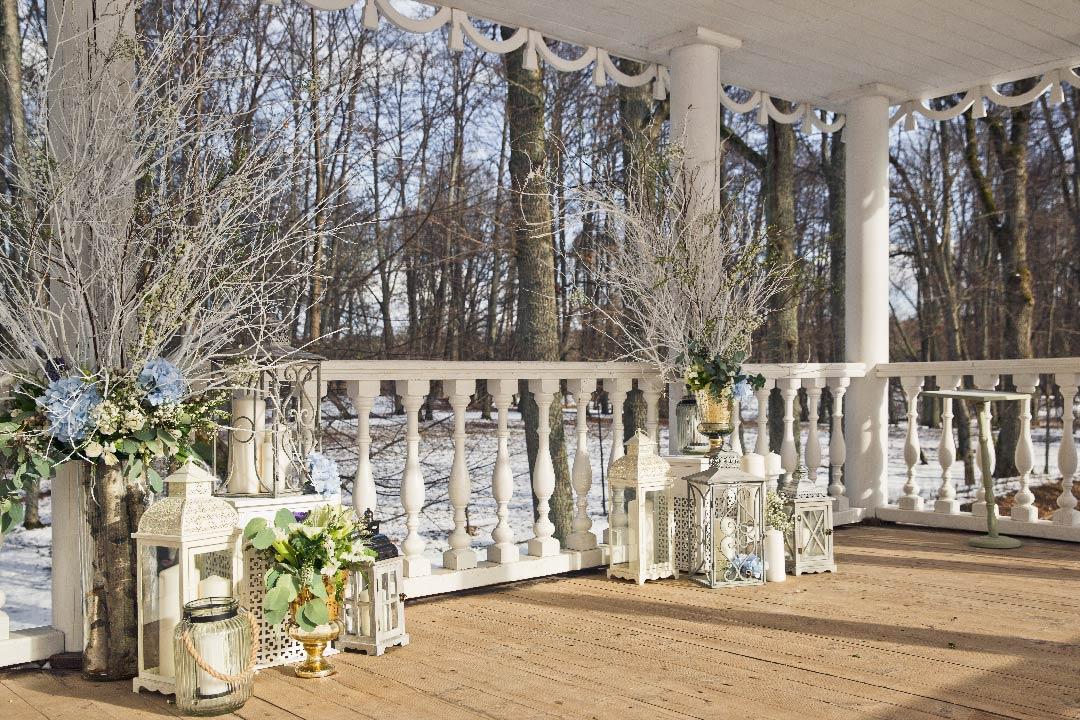 White porch decorated with white lanterns and white branches for an event party