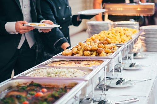 Un buffet con dei piatti pronti e delle persone davanti con dei piatti in mano