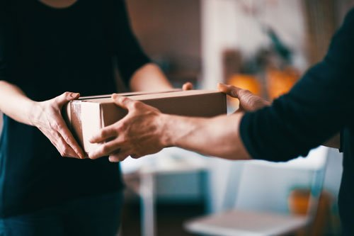 Un uomo mentre consegna un pacco a una donna