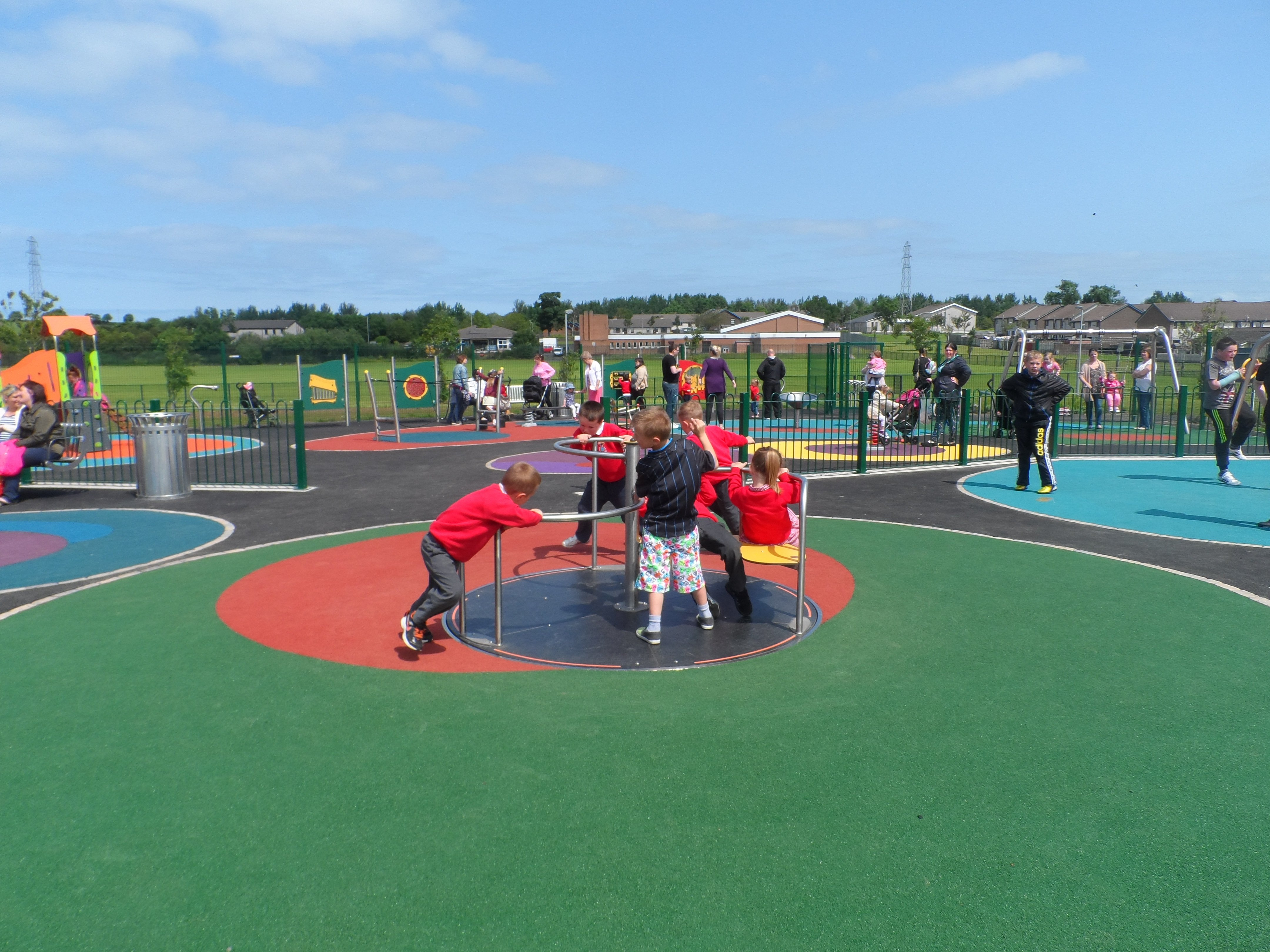 Children on a roundabout in the middle of the outdoor play area