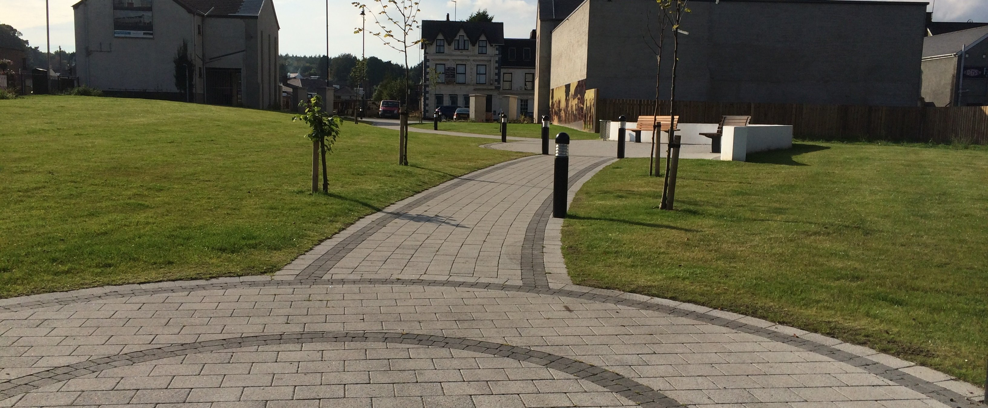 A path between two circular paved areas, in grey with darker grey edging