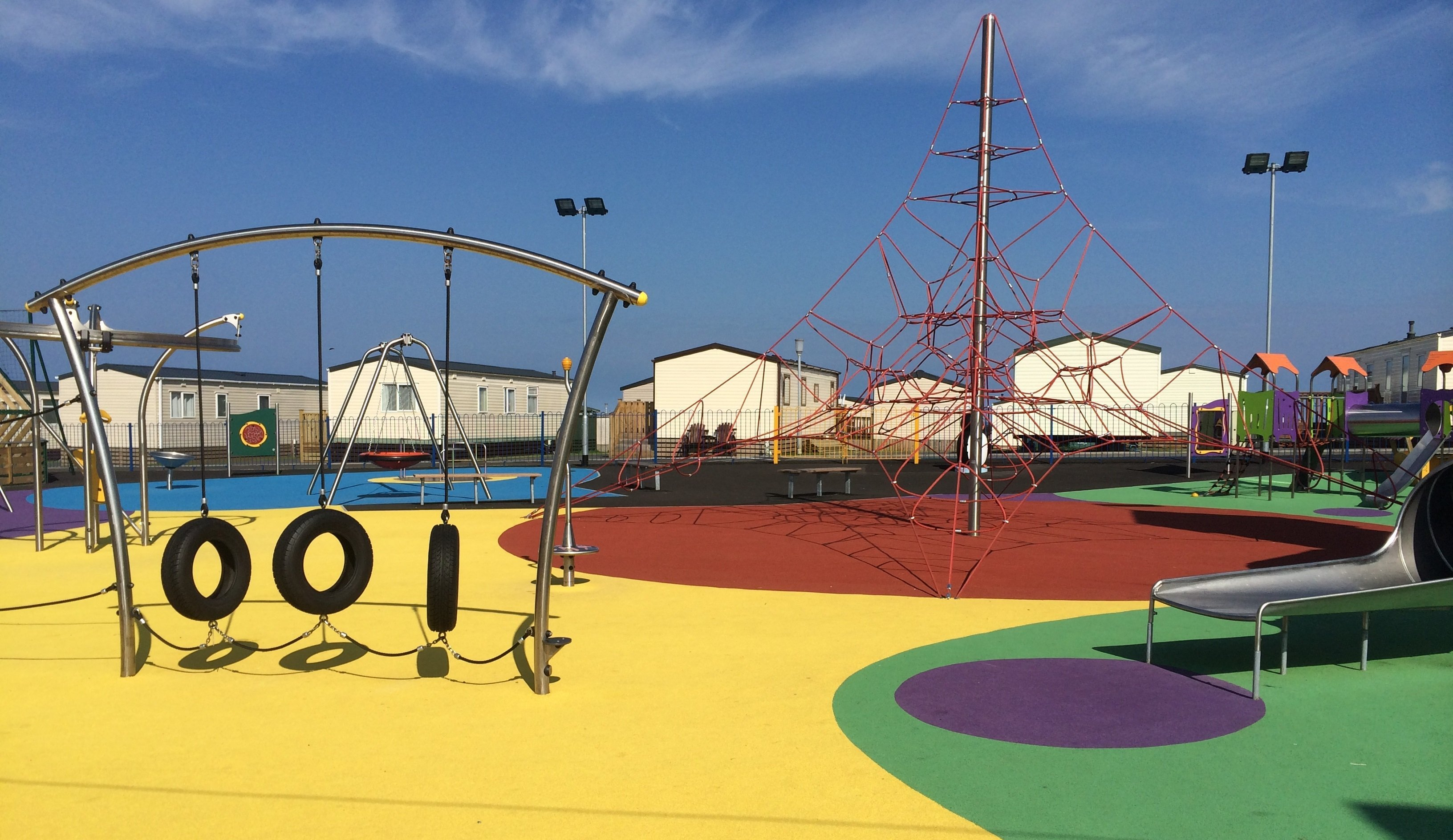 Tyre swings, a slide, and a rope climbing frame in an outdoor area surrounded by chalets