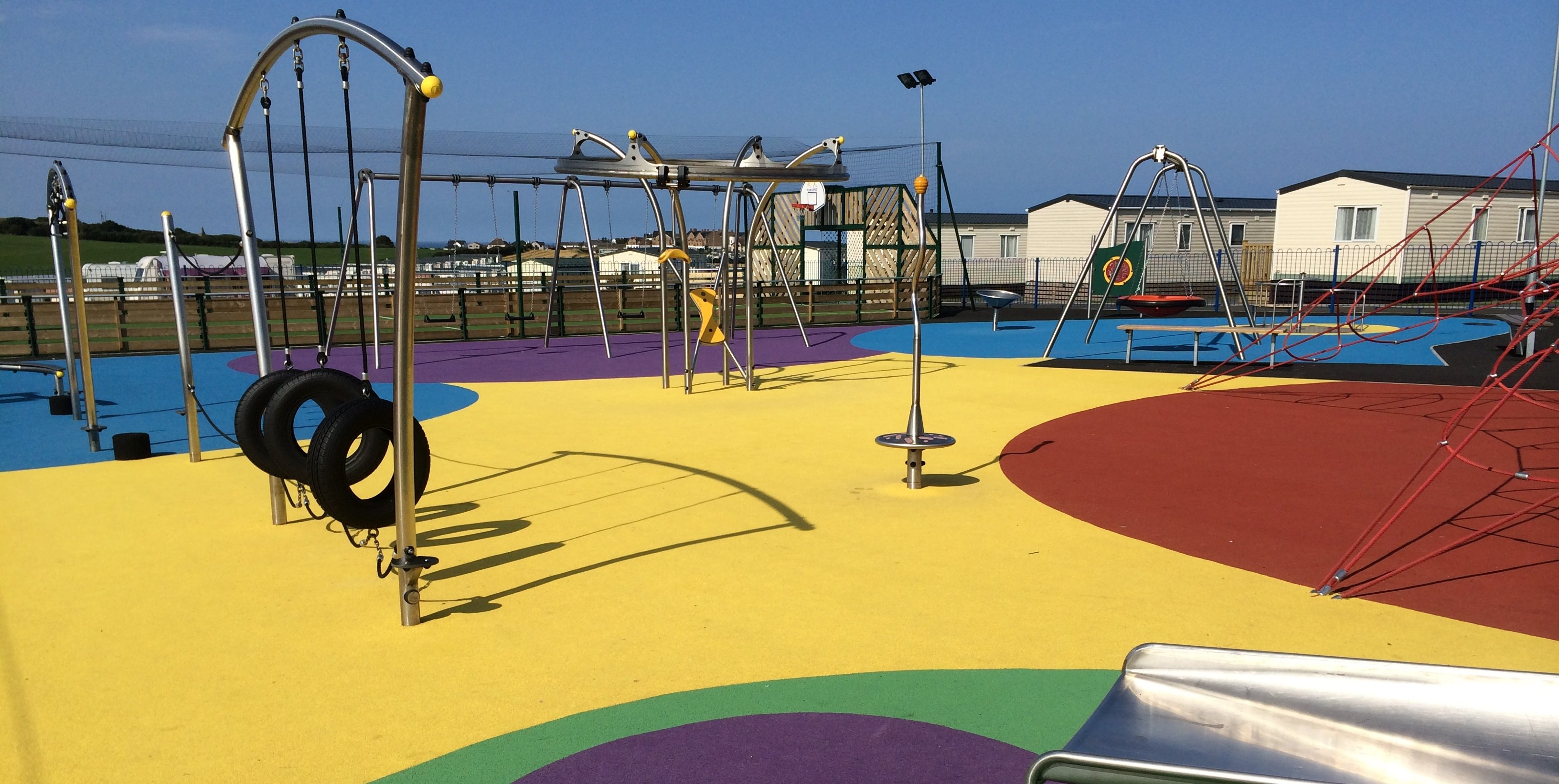 Colourful play area surrounded by holiday chalets