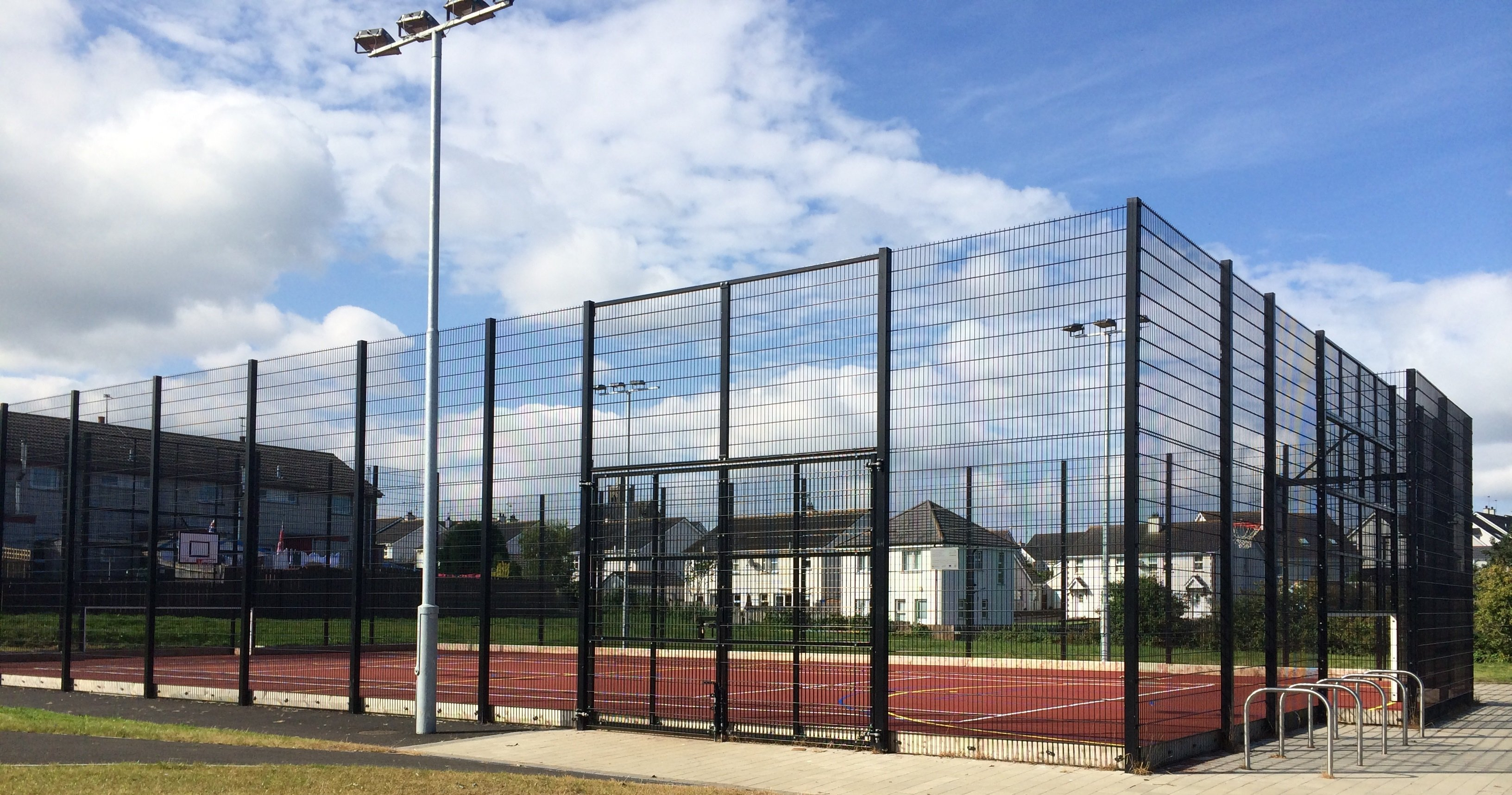 Sports court enclosed by high wire fencing