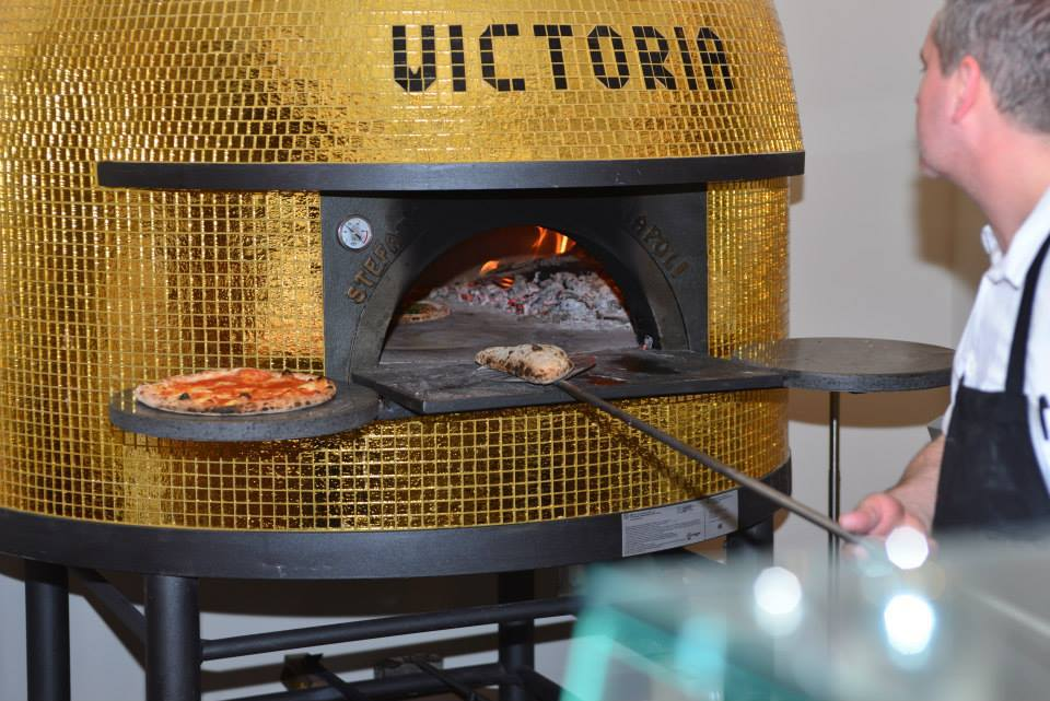 Our chef preparing a delicious pizza in our wood-fired oven