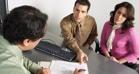 A couple speaking with a man filling in a form