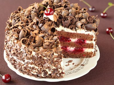 A chocolate cake with cream and cherry filling, and chocolate curls on top