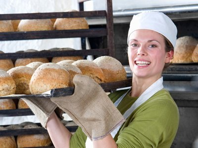 A female baker wearing oven gloves, holding a tray of freshly baked bread