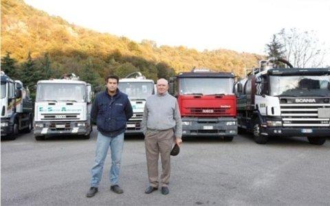 Un uomo giovane e uno maggiore davanti a diversi camion