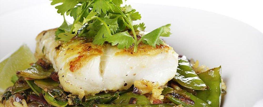 un filetto di pesce con prezzemolo e verdure