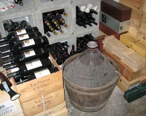 una damigiana e delle bottiglie di vino dentro a delle casse