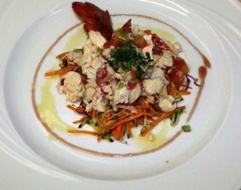 un piatto a base di pesce, carote e insalata