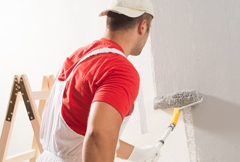 guy painting grey wall with roller