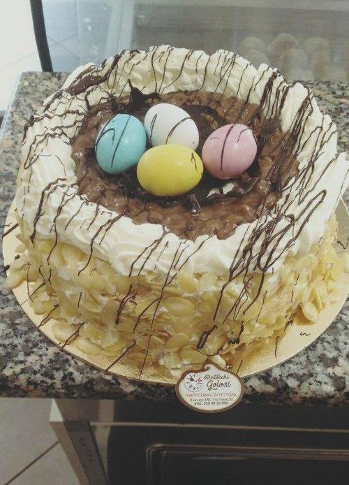 una torta con panna, cioccolato e degli ovetto colorati sopra