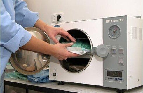 persona che sta mettendo un materiale in uno sterilizzatore