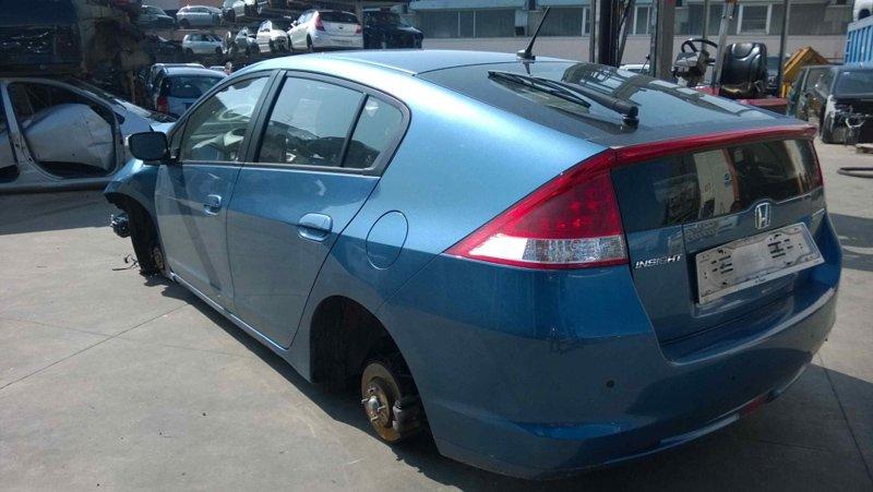 auto blu senza ruote in un centro ricambi