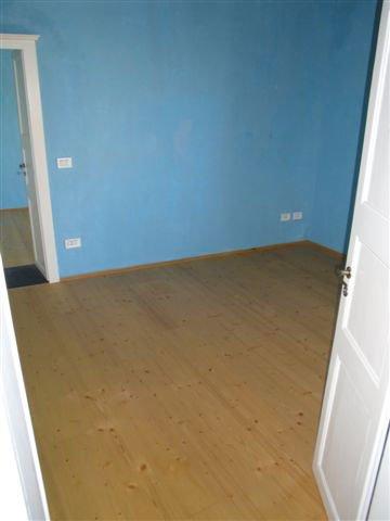 Un stanza con dei muri di color azzurro e pavimento in parquet