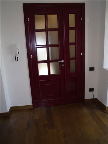 Un ingresso di una casa con la porta di color bordeaux e un pavimento in parquet