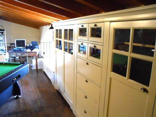 Un sala con un tetto in legno e un armadio lungo di color avorio
