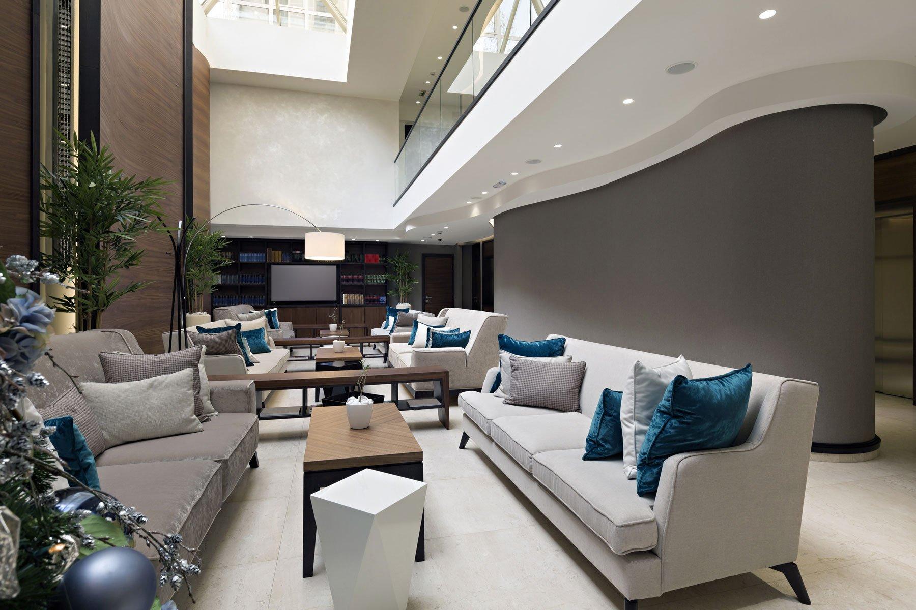 Una sala con dei divani di color bianco e grigio con dei cuscini di color turchese