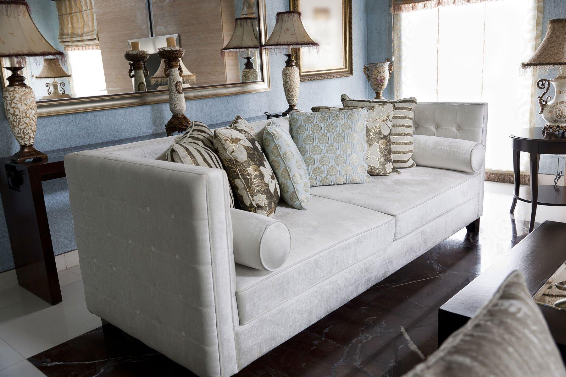 un divano da tre posti e uno specchio grande al muro