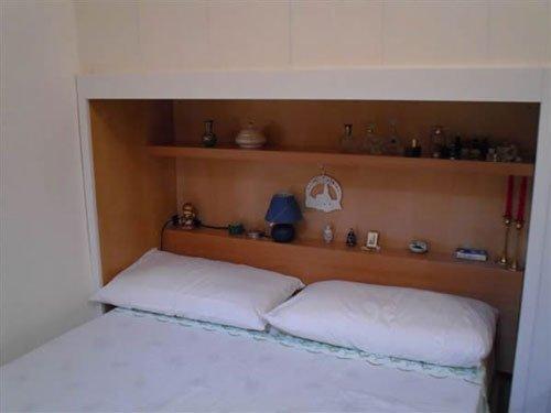 Un letto matrimoniale con due cuscini  e delle mensole in legno