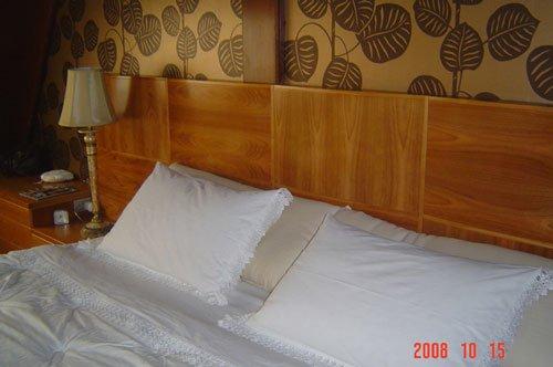 Un letto in legno e dei muri con carta da parati