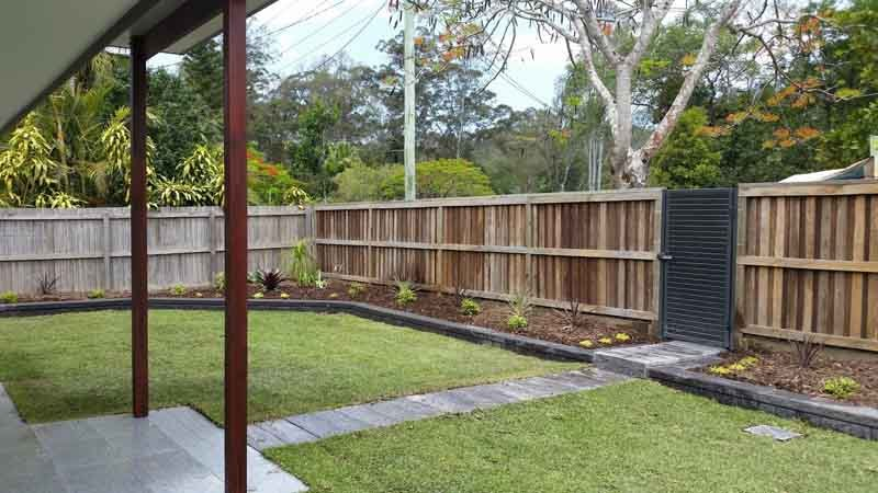 fenced backyard with a black gate