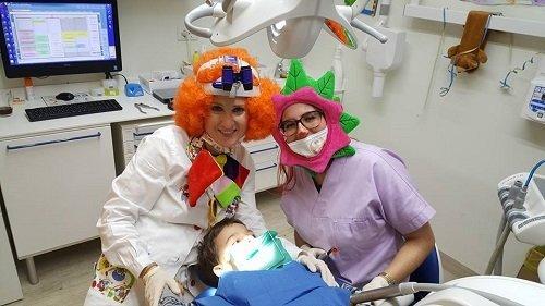 due dentiste con delle parrucche e delle maschere e un bambino sdraiato in attesa della visita