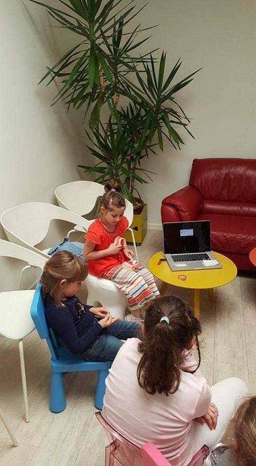 delle bambine sedute su delle sedie e un tavolino con sopra un computer portatile