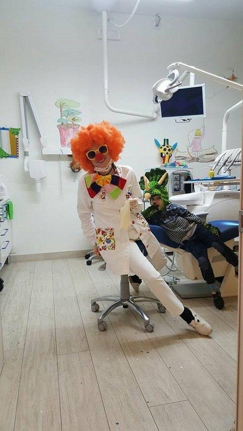 una dentista vestita da pagliaccio e un bambino con una maschera di un dragone verde
