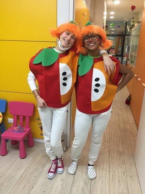 due ragazze con dei costumi e delle parrucche arancioni