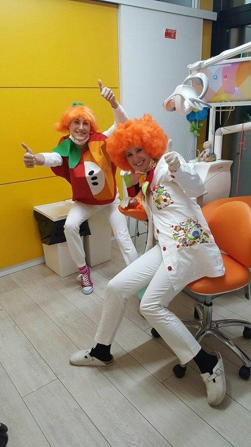 due dentiste con il pollice in su con delle parrucche arancioni