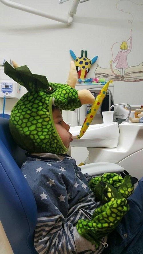 un bambino seduto vestito da dragone con una trombetta in bocca