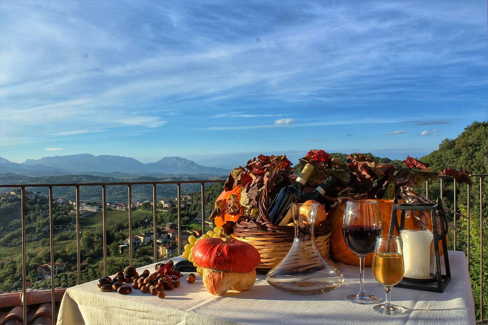 In una tavola della terrazza di fronte alle montagne ci sono due ceste, due bicchieri di vino, due bottiglie,uve e noci.